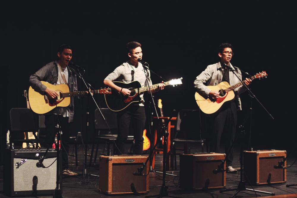 3 boys playing acoustic guitar and signing